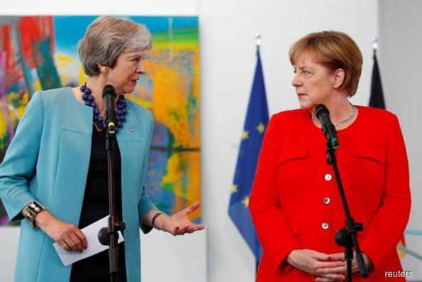 Britain's May to ask Merkel to help change Brexit divorce deal