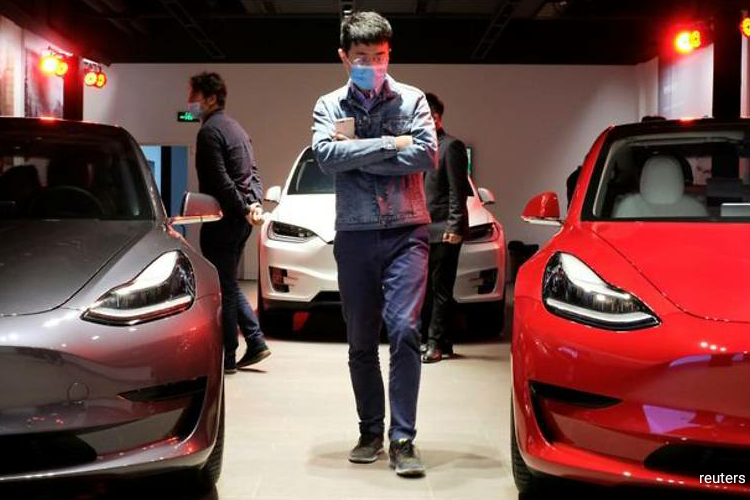 It was not immediately clear by how much Tesla was cutting its prices or when the cuts would take effect. (Photo by Reuters)