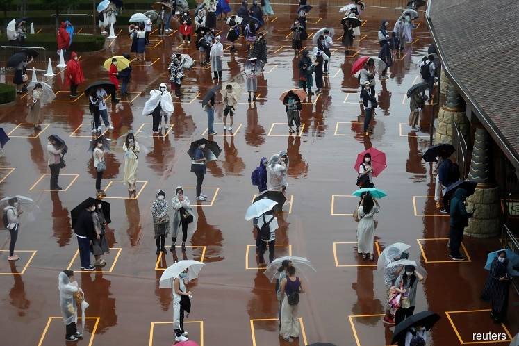 Visitors practicing social distancing while waiting to enter the park in the poor weather during the reopening of Tokyo Disneyland along with Tokyo DisneySea, which closed for months due to the Covid-19 outbreak, at the entrance gate of Tokyo DisneySea in Urayasu, east of Tokyo, Japan on July 1. (Photo by Reuters)