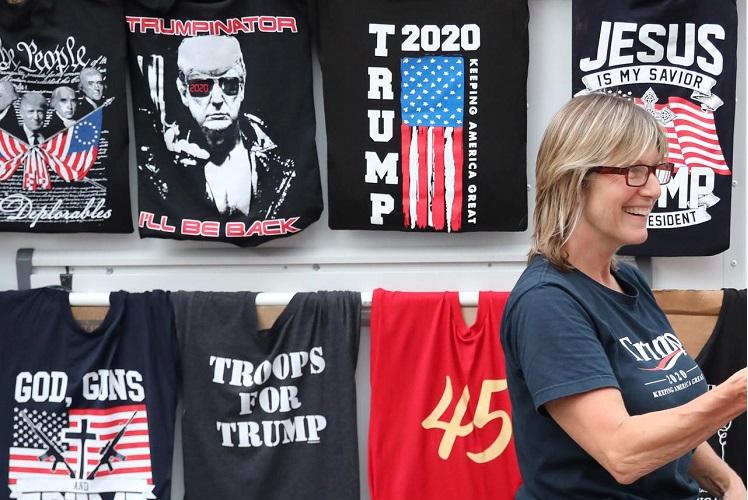 An armed woman sells T-shirts, a day before a rally by US President Donald Trump, near the BOK Center in Tulsa, Oklahoma, US, June 19, 2020. (Photo by Reuters)