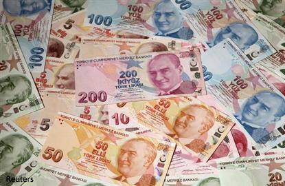 Turkish lira drops on downgrade as oil pressures emerging assets