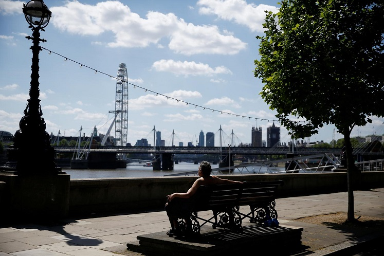 A man is seen relaxing by the RIver Thames in Central London following the outbreak of Covid-19, London, Britain, May 25, 2020. (Photo by Reuters)