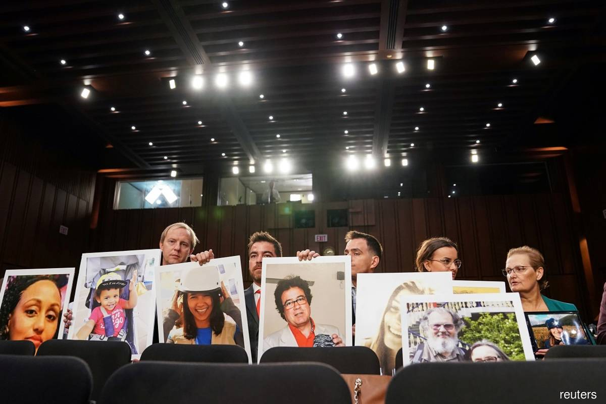 """Family members holding photographs of victims perished in two deadly Boeing 737 MAX crashes that killed 346 people as Boeing chief executive officer Dennis Muilenburg testified before a Senate Commerce, Science, and Transportation Committee hearing on """"aviation safety"""" and the grounded 737 MAX on Capitol Hill in Washington, the US on Oct 29, 2019."""