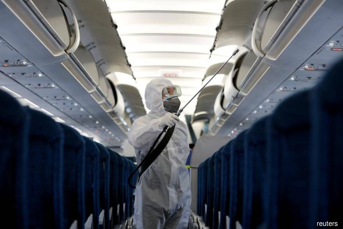 A health worker sprays disinfectant inside a Vietnam Airlines airplane. (File pic by Reuters)