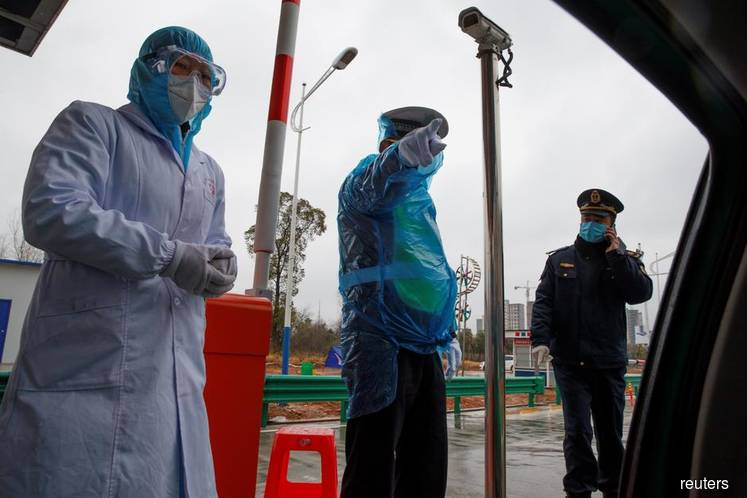 A medical worker and police stand at a checkpoint as the country is hit by an outbreak of the novel coronavirus in Susong County, Anhui province, China, Feb 6, 2020. (Photo by Reuters)