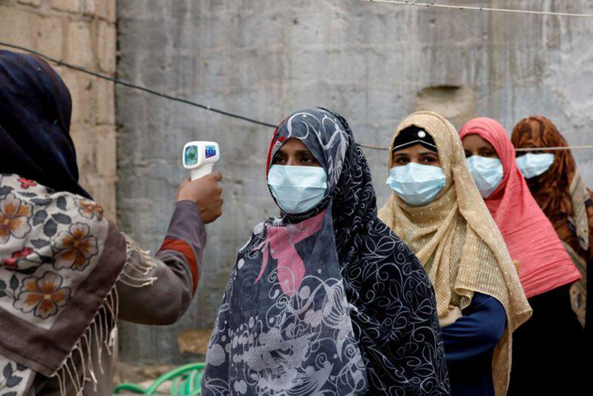 Vaccinators wear protective masks as they get their temperature checked, during an anti-polio campaign, in a low-income neighborhood as the spread of the coronavirus disease (COVID-19) continues, in Karachi, Pakistan, July 20, 2020. (Photo by Reuters)