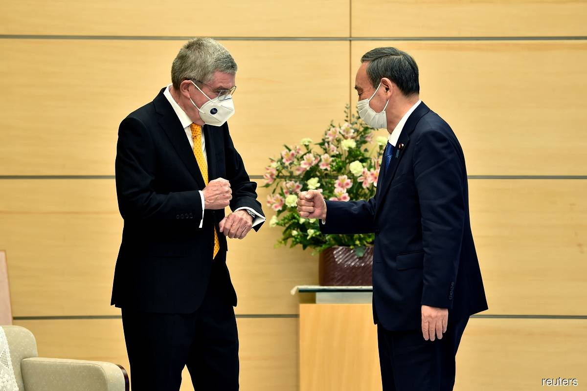 International Olympic Committee chief Thomas Bach (left) and Japan Prime Minister Yoshihide Suga (right) greeting each other with a fist bump during their meeting in Tokyo, Japan today.