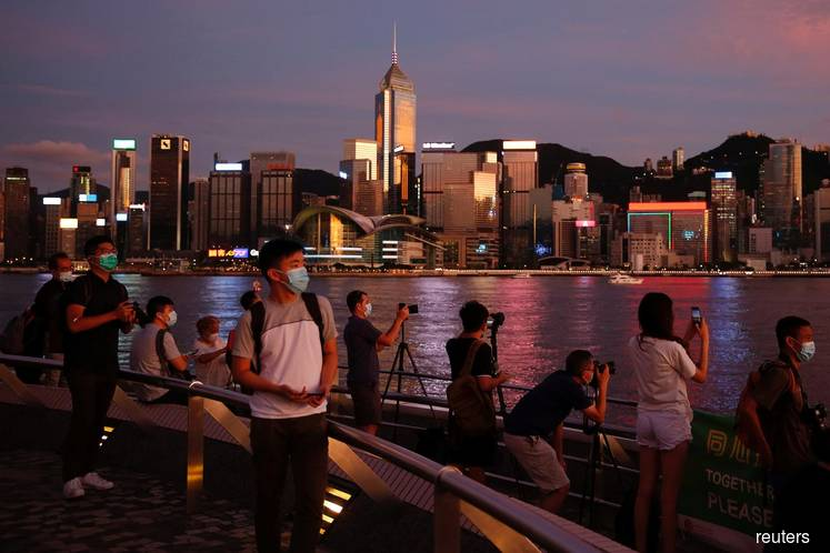 People enjoy the sunset view with a skyline of buildings during a meeting on national security legislation, in Hong Kong, China on June 29, 2020. (File photo by: Tyrone Siu/REUTERS)
